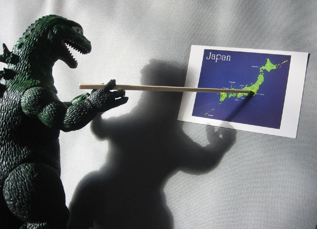 A Godzilla figurine holding a stick that points to a map of Japan.