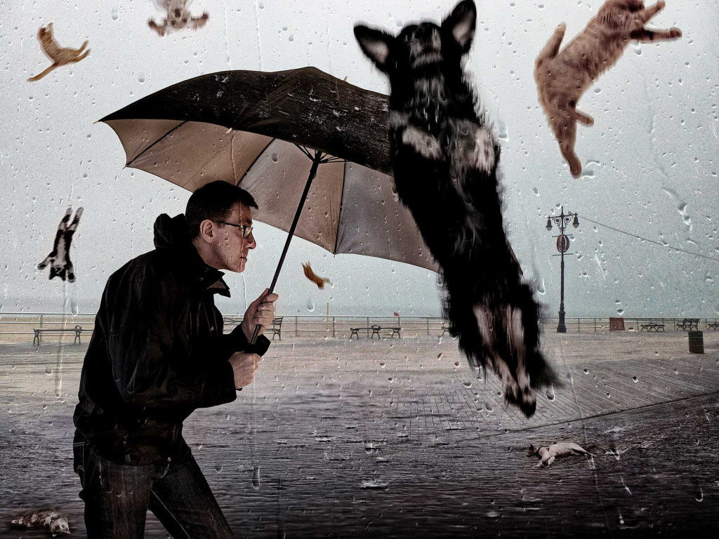 A man hiding under an umbrella from the cats and dogs raining from the sky.
