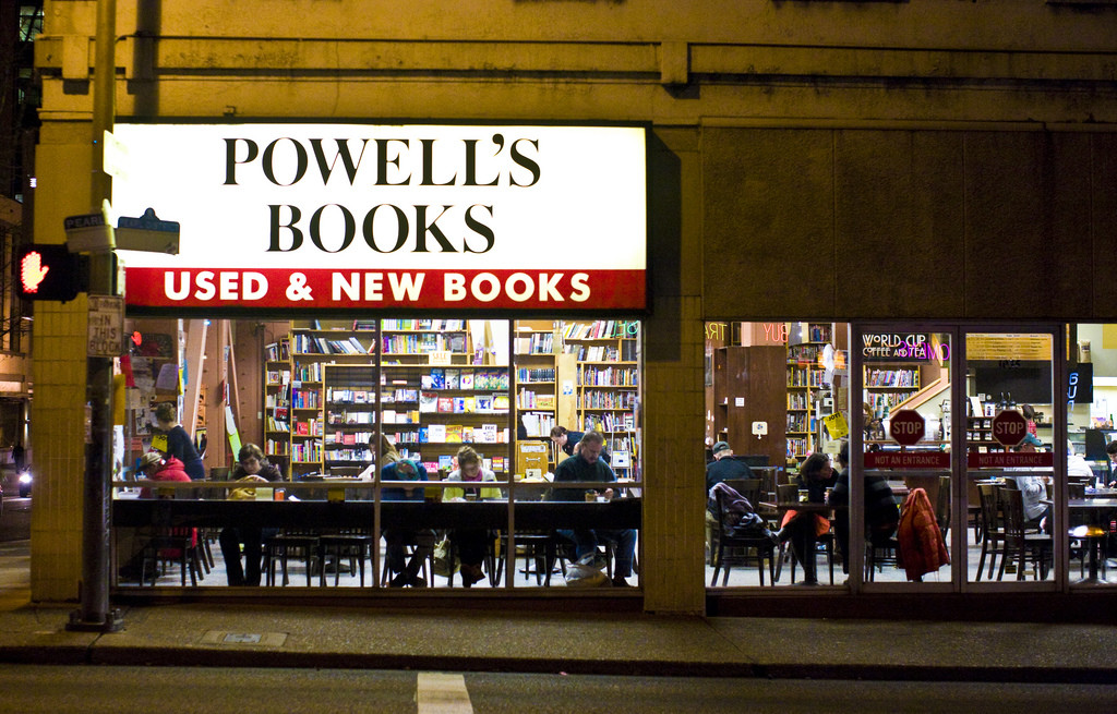 A lit-up storefront for Powell's Books bookstore. Large windows show tall shelves full of books and tables where people are sitting, eating, and reading.