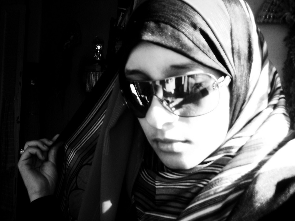 Close-up of a young woman wearing hijab and sunglasses.