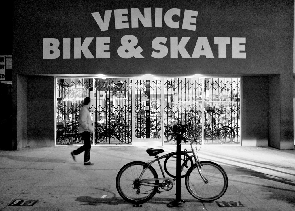 A man looks at the storefront for Venice Bike & Skate shop as he walks by.