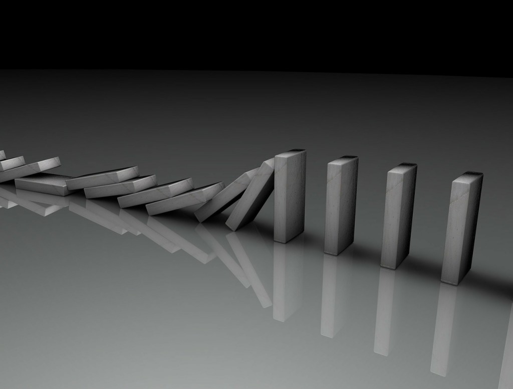 black and white photo of a line of gray dominoes. Ten have tipped over; six are still standing.