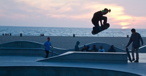 Skateboarders at a skating rink by the beach.