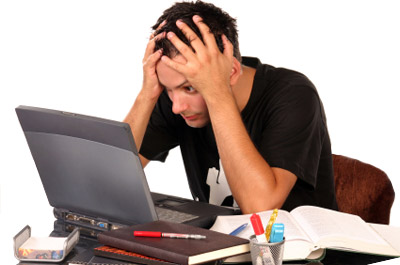 A stressed out student staring at his computer with his hands on his head.