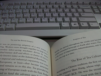 A book open in front of a keyboard.