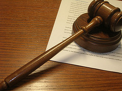 A gavel lying on a table with documents underneath it