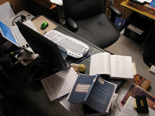 A computer desk with books scattered everywhere in a disorganized mess.