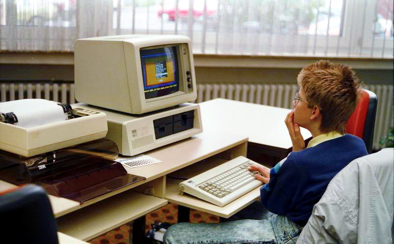 A boy sitting in front of a personal computer; the computer is considerably blockier than computers today.