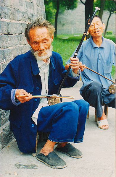 An old man on a street playing the erhu.