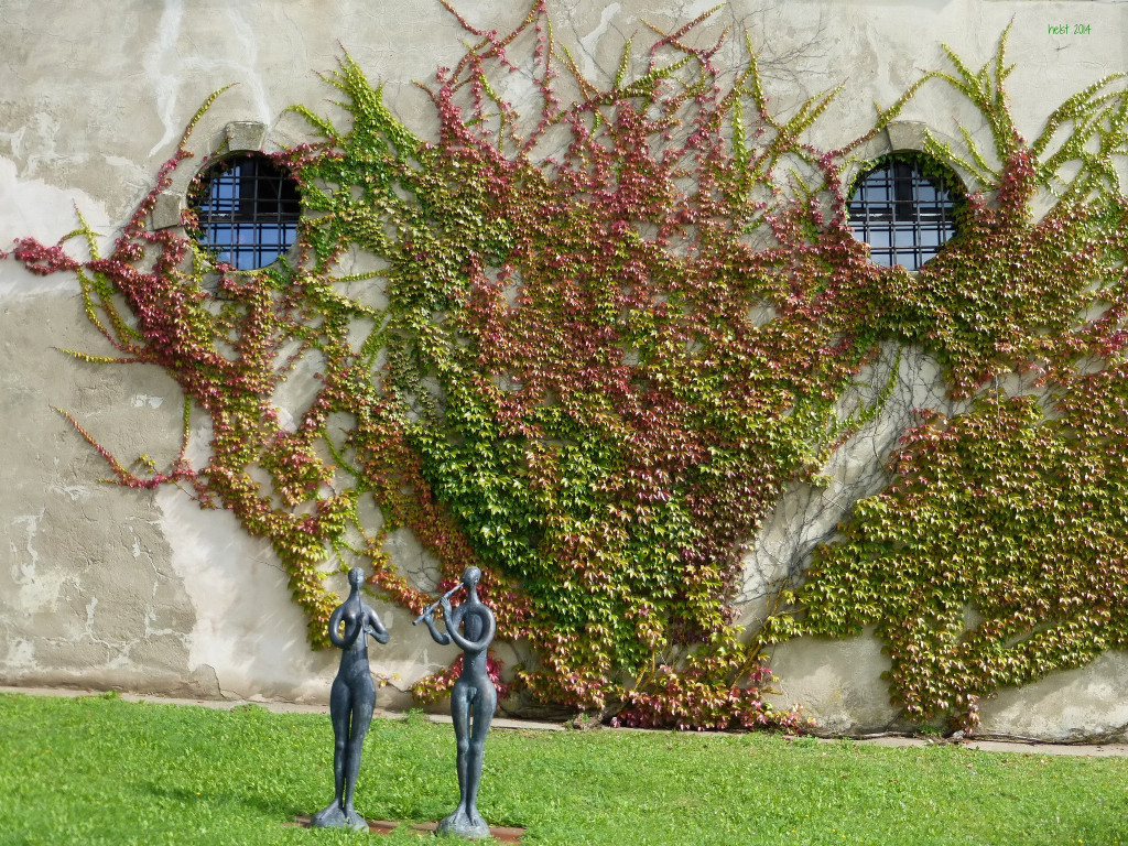 Photo of a vine-covered wall of Burg Spielberg; on the lawn in the foreground are two small bronze sculptures of a nude man and woman; the man is playing a flute.