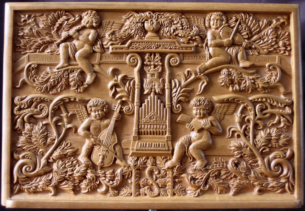 Wood carving showing four angels playing instruments: violins, viola da gamba, and the recorder