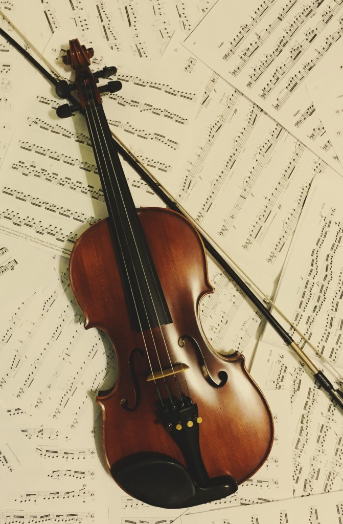 Photo of a violin lying on sheet music.