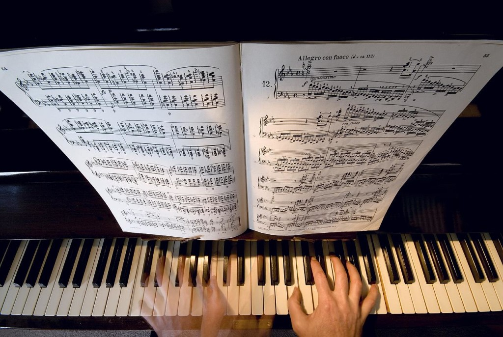 "Photo of piano keyboard: two hands are shown along with sheet music instructing the pianist to play ""Allegro con fuoco."""