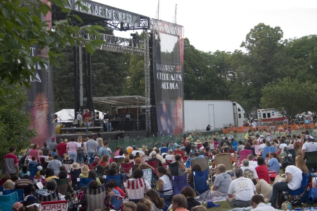 Photo of outdoor concert and concertgoers sitting on the grass