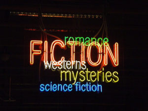 Neon sign with Fiction in red, all caps. Around it are smaller types of genres: westerns, mysteries, science fiction, and romance.