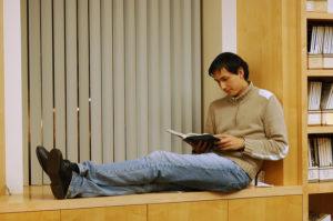 Man sitting in a window seat reading