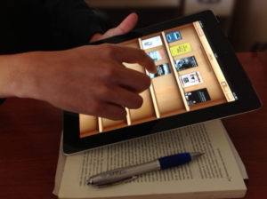 hand holding an iPad with book covers on its screen