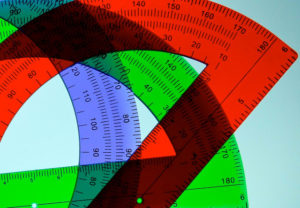 Three overlaid plastic protractors in red, green, and blue