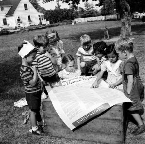 Black and white photo of several children clustered around a poster of the Declaration of Human Rights on a milk crate in a backyard play area