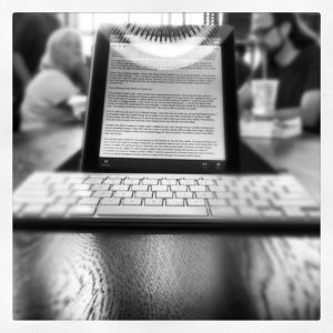 Black and white photo of a tablet displaying text and wireless keyboard, on a table in a cafe with people in the background