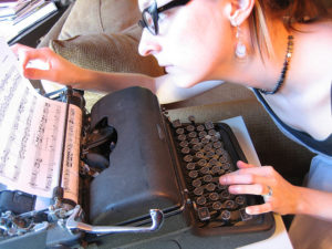 Woman peering at a page in the typewriter before her, which contains musical scores.