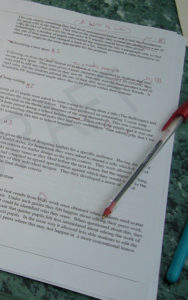 """Typed page of text with """"Draft"""" watermarked across it. A red pen rests on it, and red marks are all over the page."""