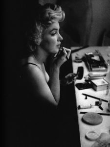 Black and white photo of Marilyn Monroe applying lipstick in a dressing room mirror