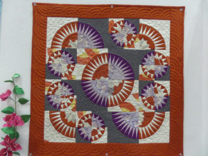 Square quilt with circles of orange, purple, gray, and white
