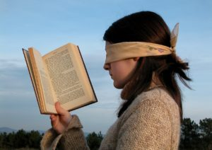 Woman wearing a blindfold, holding an open book up to her face