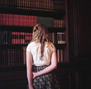 Blond woman standing with her back to the camera, facing a tall bookshelf lined with leather-bound volume sets