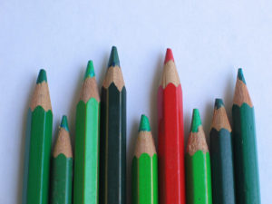 row of 9 colored pencils. All are shades of green except 4th from right, which is red.