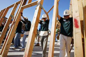 Men in hard hats and volunteer tee shirts raising a wall frame for a house
