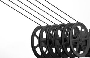 Black and white photo of six power line cables on reels