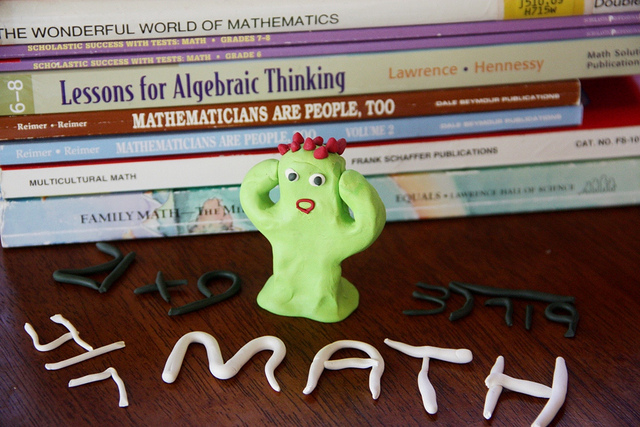"Green figure made out of play-doh, hands to its head, posed in front of a stack of math textbooks. The phrase ""math"" and simple equations are spelled out in rolled-out play-doh as well."
