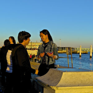 Young man and woman talking on a crowded sea wall