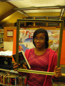 Young woman holding a book and a picture frame in a library, so that she's framed as a reader