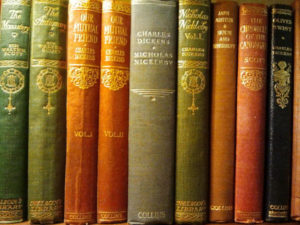 Leather-bound books on a shelf, including works by Sir Walter Scott and Charles Dickens