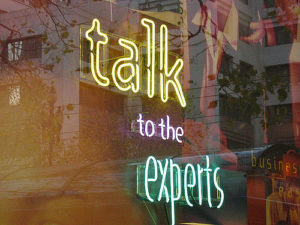 "neon sign reading ""talk to the experts"""