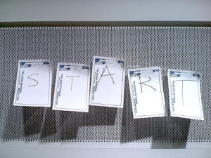 "Five sticky notes on a billboard. Each contains a letter to spell out ""START""."