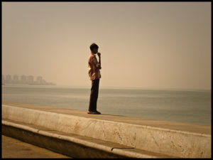 Young man standing in profile on a sea wall