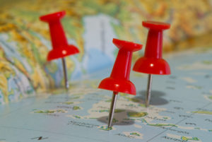 Three red push-pins noting islands on a map