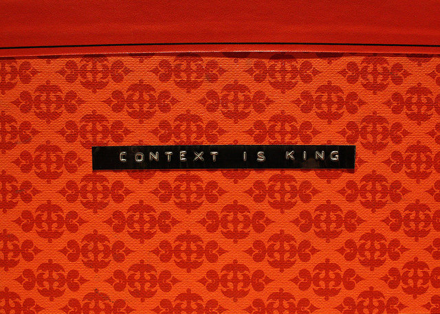 "Red patterned background. Small black label tape central, reading ""Context is King"""