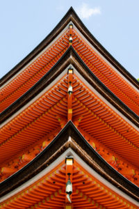 Looking up from below the corner of a Japanese temple, so that three levels of red eaves, capped by black gutters, are arranged in a strong vertical point