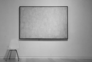 Black and white photo of framed canvas on wall with texture but no image. A white chair sits at bottom left against wall.