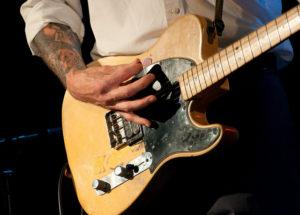 Man strumming an electric guitar during a rock concert.
