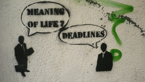 """Graffiti on wall. One figure in business suit asks, """"Meaning of life?"""" Another answers """"Deadlines."""""""
