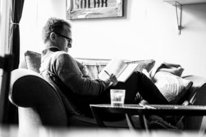 Black and white photo of a man writing in a notebook while outstretched on a couch