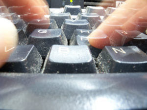 Close up of computer keyboard with blurry fingers