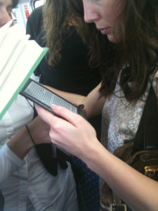 Woman standing, reading on a Kindle on a crowded public transit train