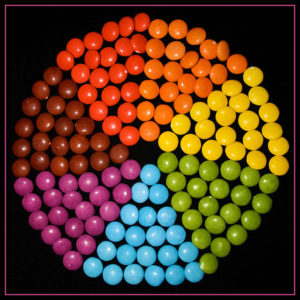 round candies in bright colors arranged in triangle wedges to form a color wheel, on a black background